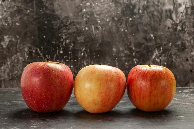 Vista frontal de maçãs frescas alinhadas em foto escura de frutas maduras de frutas maduras de vitamina