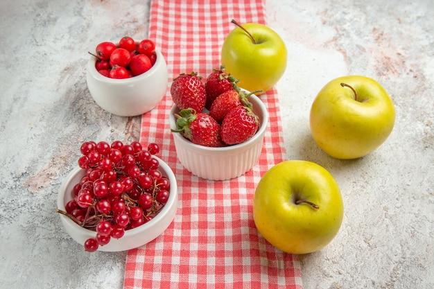 Vista frontal de maçãs frescas com frutas vermelhas na árvore de cor de frutas vermelhas mesa branca