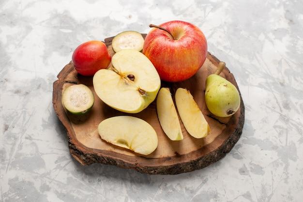 Vista frontal de maçãs frescas com peras frescas em um espaço branco claro