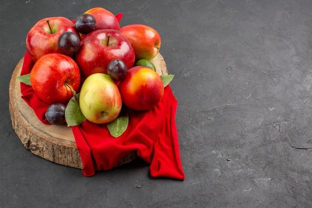 Vista frontal de maçãs frescas com pêssegos e ameixas na mesa escura da árvore de suco maduro