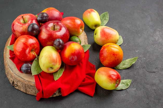 Vista frontal de maçãs frescas e ameixas na mesa escura suco maduro maduro