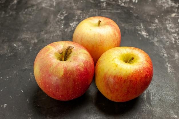 Vista frontal de maçãs frescas em frutas escuras, foto cor de suco maduro de vitamina madura