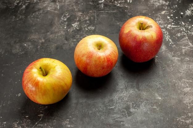 Vista frontal de maçãs frescas forradas em foto escura, frutas maduras, frutas maduras, cor de suco de árvore vitaminada