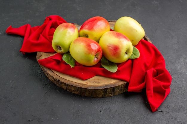 Vista frontal de maçãs frescas, frutas maduras em tecido vermelho e mesa cinza árvore de frutas maduras