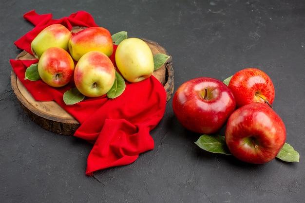 Vista frontal de maçãs frescas, frutas maduras em tecido vermelho e mesa cinza.