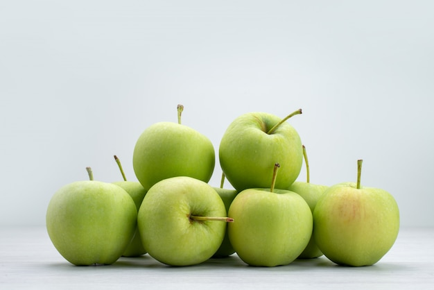 Vista frontal de maçãs verdes alinhadas em cinza