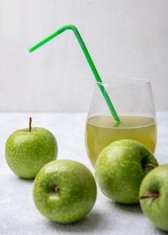 Vista frontal de maçãs verdes com suco de maçã em um copo e um canudo verde em um fundo branco