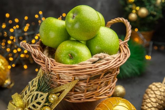 Vista frontal de maçãs verdes frescas ao redor de brinquedos de natal em fundo escuro foto colorida fruta de feriado de natal