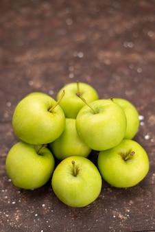 Vista frontal de maçãs verdes maduras e suculentas isoladas em marrom