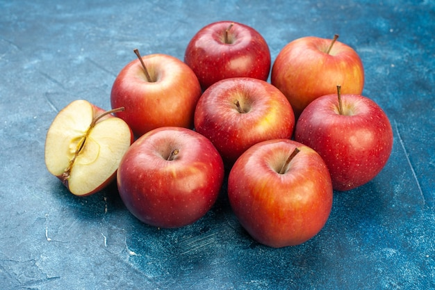 Vista frontal de maçãs vermelhas frescas alinhadas na superfície azul