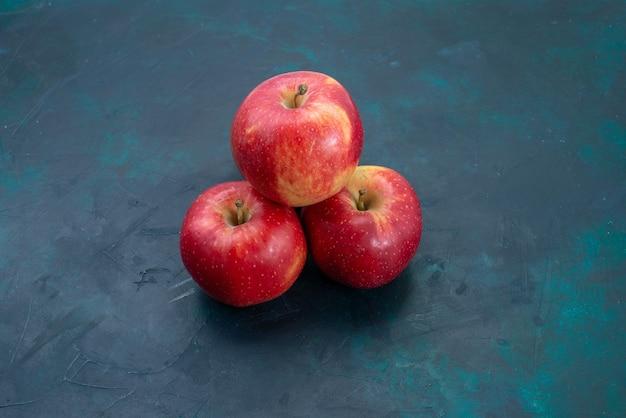Vista frontal de maçãs vermelhas frescas maduras e frutas frescas na mesa azul escuro frutas frescas maduras árvore madura