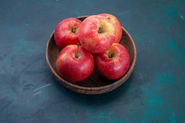 Vista frontal de maçãs vermelhas frescas maduras e frutas frescas na mesa azul escuro