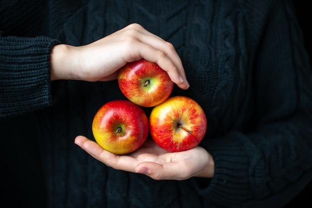 Vista frontal de maçãs vermelhas maduras nas mãos de mulheres