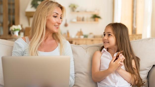 Vista frontal de mãe e filha em casa com laptop e smartphone