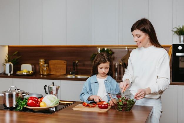 Vista frontal de mãe e filha preparando comida na cozinha
