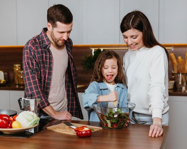Vista frontal de mãe e pai com criança preparando comida na cozinha
