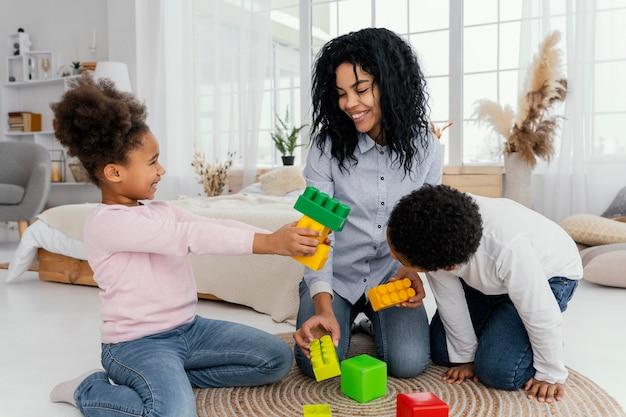 Vista frontal de mãe feliz brincando em casa com seus filhos