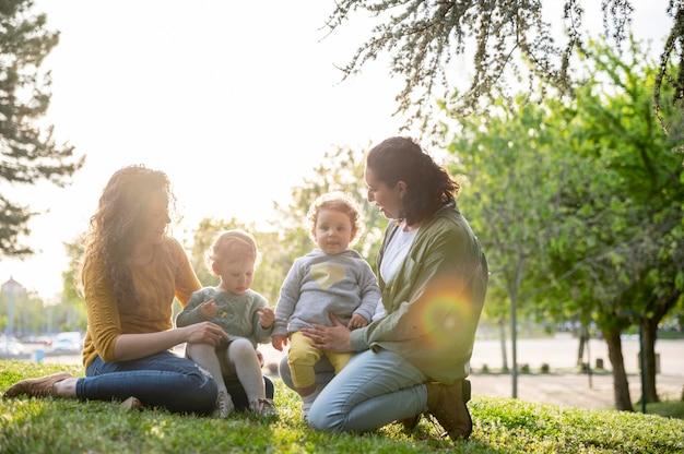Vista frontal de mães lgbt ao ar livre no parque com seus filhos