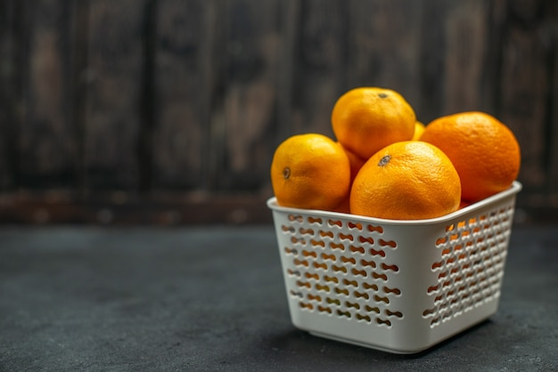 Vista frontal de mandarinas e laranjas em uma cesta de plástico em um fundo escuro com espaço livre