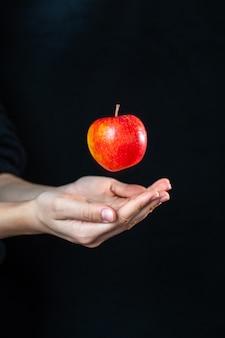 Vista frontal de mãos humanas com uma maçã na superfície escura
