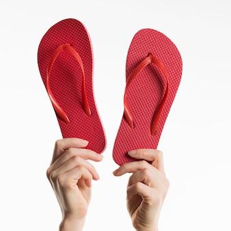 Vista frontal de mãos segurando chinelos