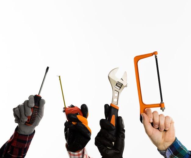 Vista frontal de mãos segurando ferramentas com espaço de cópia