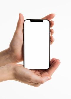 Vista frontal de mãos segurando um smartphone com tela em branco