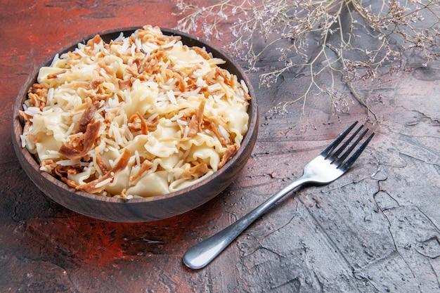 Vista frontal de massa cozida fatiada com arroz em prato de superfície escura farinha de massa