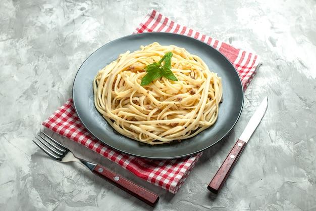 Vista frontal de massa italiana cozida com talheres em fundo branco