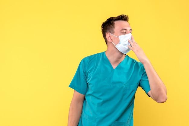 Vista frontal de médico bocejando com máscara na parede amarela