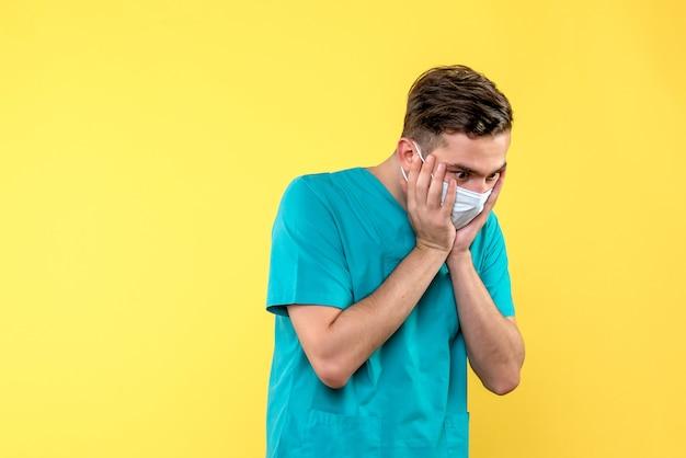 Vista frontal de médico chocado em parede amarela