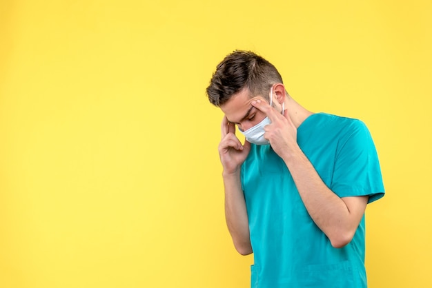 Vista frontal de médico com dor de cabeça na parede amarela