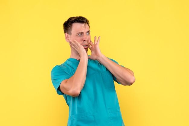 Vista frontal de médico com expressão de medo na parede amarela