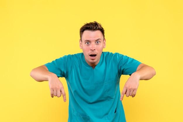 Vista frontal de médico com expressão de surpresa na parede amarela