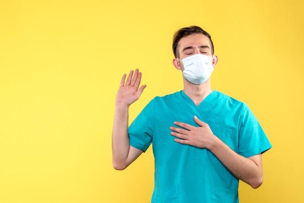 Vista frontal de médico em pose de palavrão com máscara na parede amarela