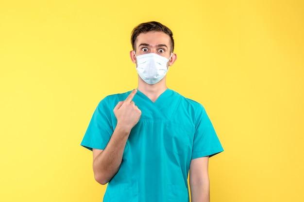 Vista frontal de médico usando máscara na parede amarela