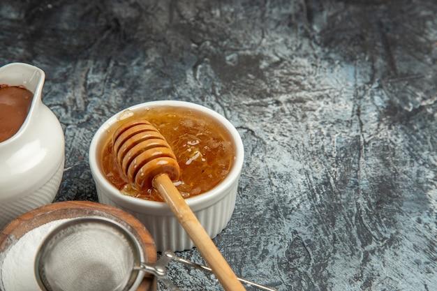 Vista frontal de mel doce com açúcar na superfície escura.