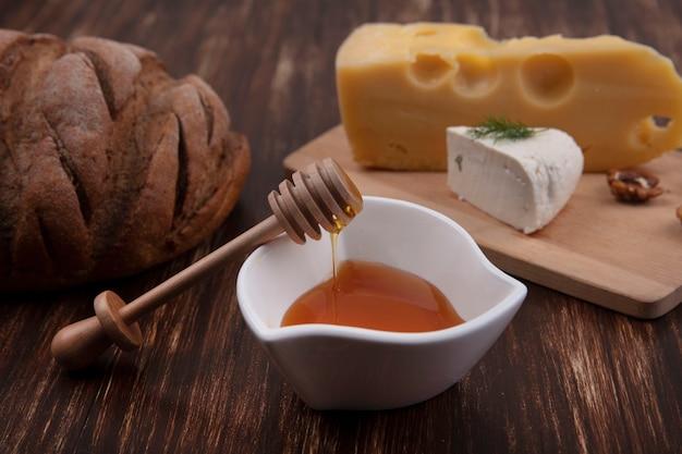 Vista frontal de mel em pires com uma variedade de queijos em uma barraca com nozes e um pedaço de pão em um fundo de madeira