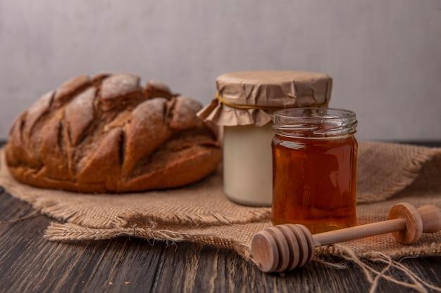 Vista frontal de mel em uma jarra com iogurte e pão preto em um guardanapo bege