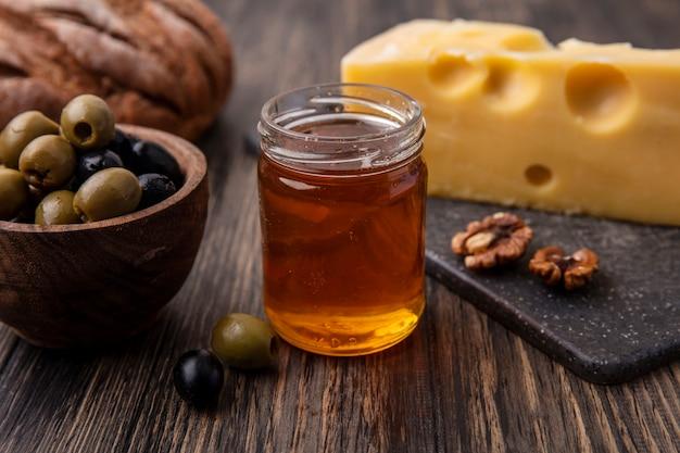 Vista frontal de mel em uma jarra com queijo maasdam em um suporte e azeitonas na mesa