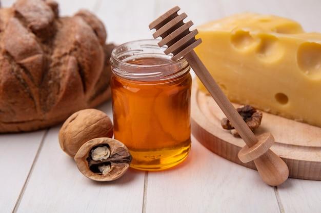 Vista frontal de mel em uma jarra com queijo nozes e pão preto em um fundo branco