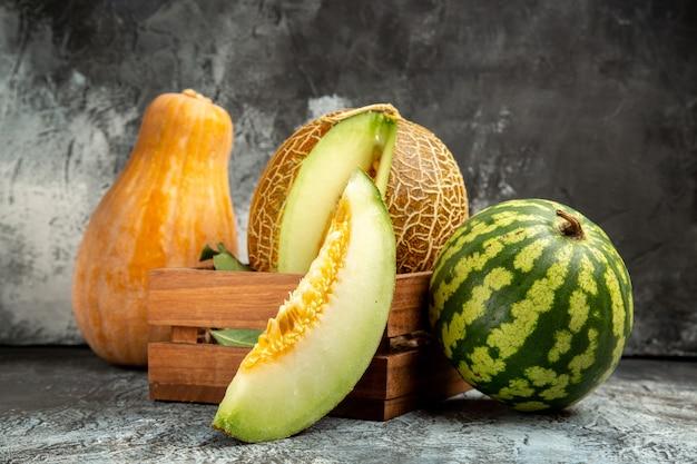 Vista frontal de melão fresco com abóbora e melancia no fundo escuro
