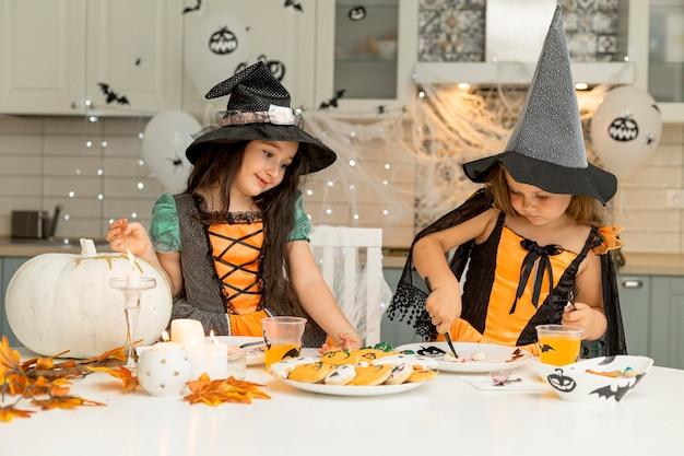 Vista frontal de meninas com fantasias de bruxa