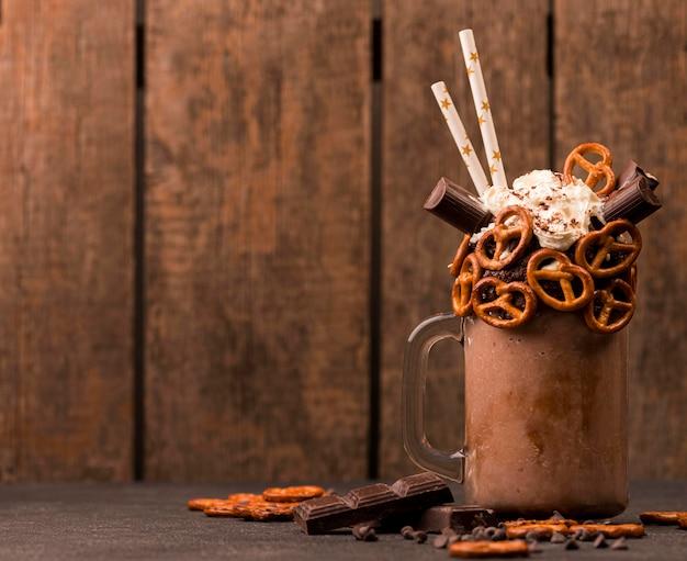 Vista frontal de milkshake de chocolate com pretzels e espaço de cópia
