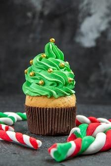 Vista frontal de mini cupcake de árvore de natal e doces de natal em fundo escuro