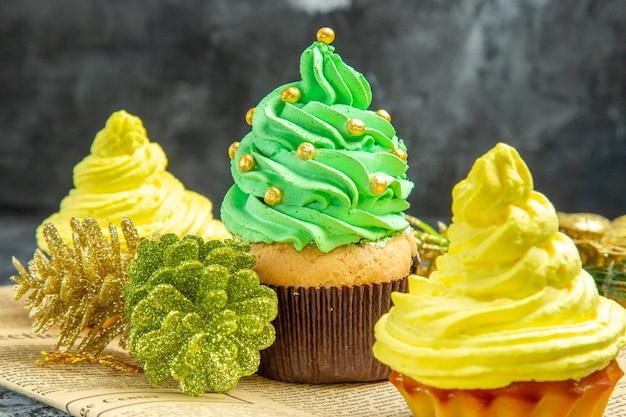 Vista frontal de mini cupcakes no jornal na foto escura do natal