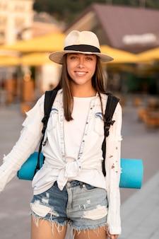 Vista frontal de mulher com chapéu carregando mochila enquanto viaja