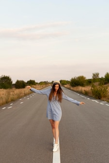 Vista frontal de mulher com chapéu posando no meio da estrada com os braços abertos