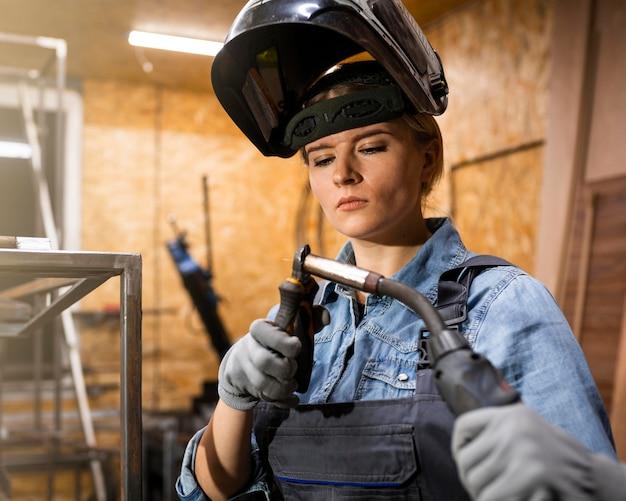 Vista frontal de mulher com ferramenta de soldagem