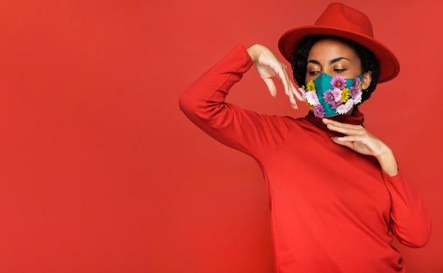 Vista frontal de mulher com flores e máscara